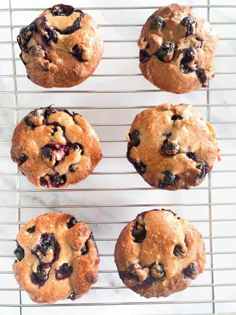 6 Blueberry Apple Hazelnut Muffins on a rack
