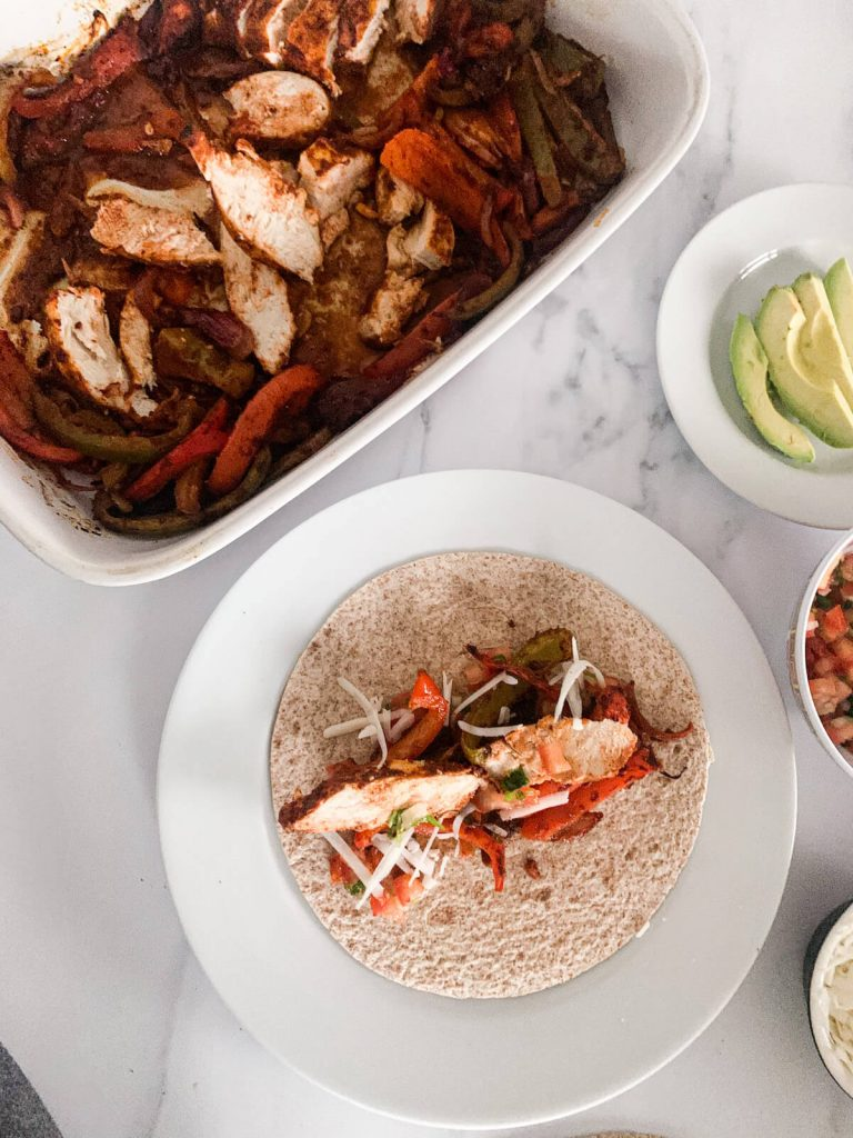 Easy oven baked chicken fajitas - picture or the tortilla filled with chicken, salsa, avocado, peppers, onions and cheese