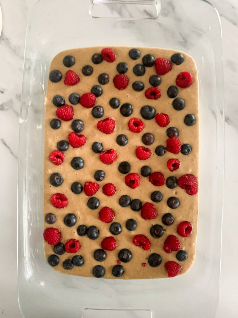 raw batter for the yoghurt cake, placed in a glass dish and topped with blueberries and raspberries