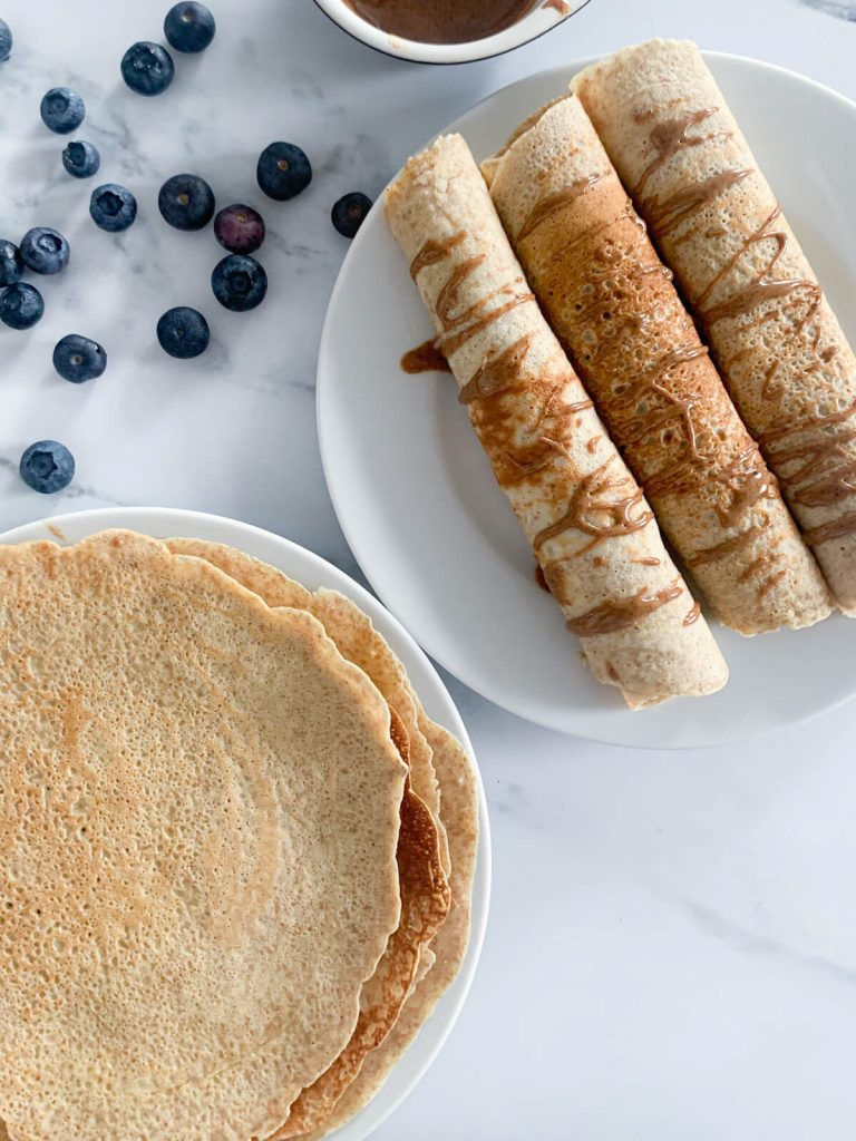 a stack of wholewheat dairy-free pancakes next to 3 rolled up pancakes drizzled with almond butter