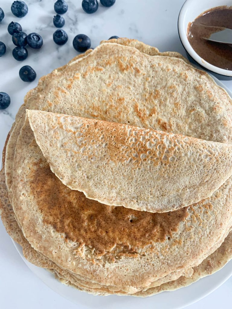 one pancake with almond butter folded on top of a stack of wholewheat dairy-free pancakes