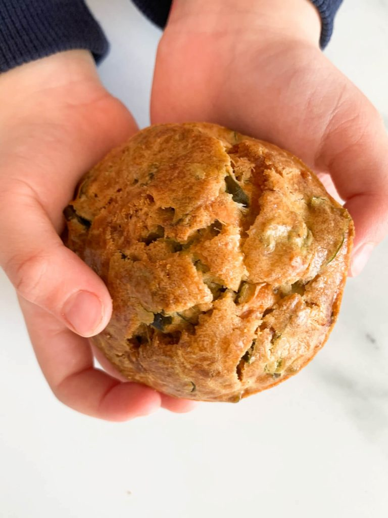 Toddler holding a Spinach Cornbread Muffin