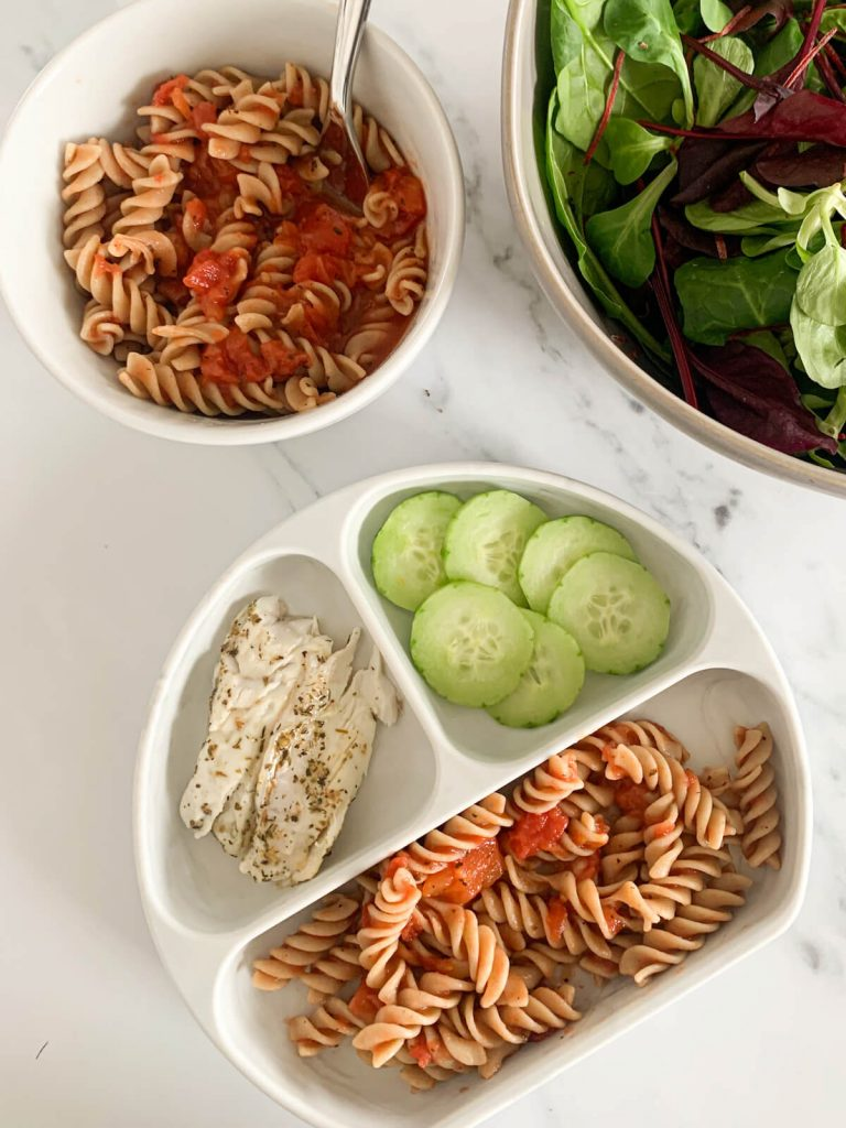 A plate for toddler with homemade pasta sauce, sea bass and cucumbers and for mom pasta with salad