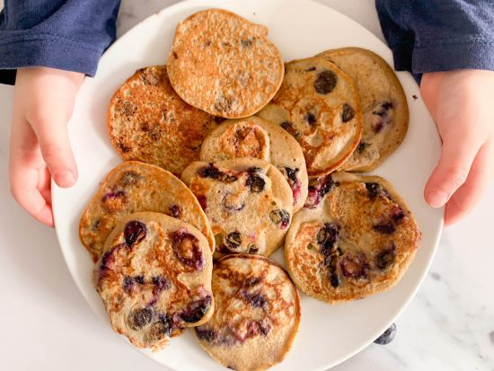 Toddler holding healthy blueberry pancakes
