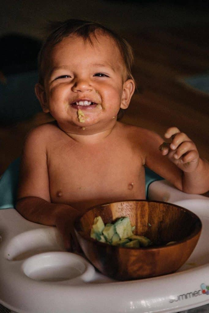 Toddler eating avocado