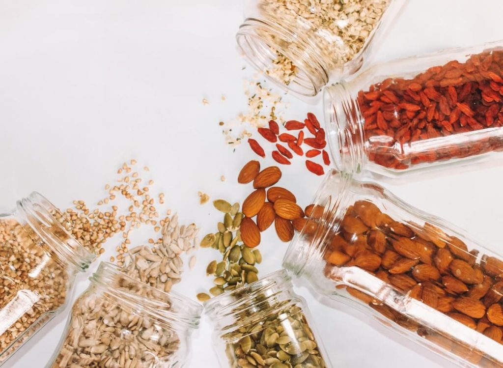 Grains, nuts and dried fruits on white background