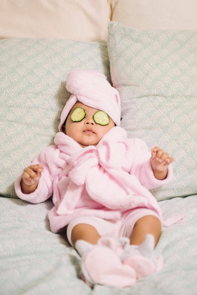 Baby relaxing in a pink bathrobe in bed