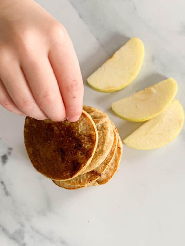 Toddler picking up an apple pancake