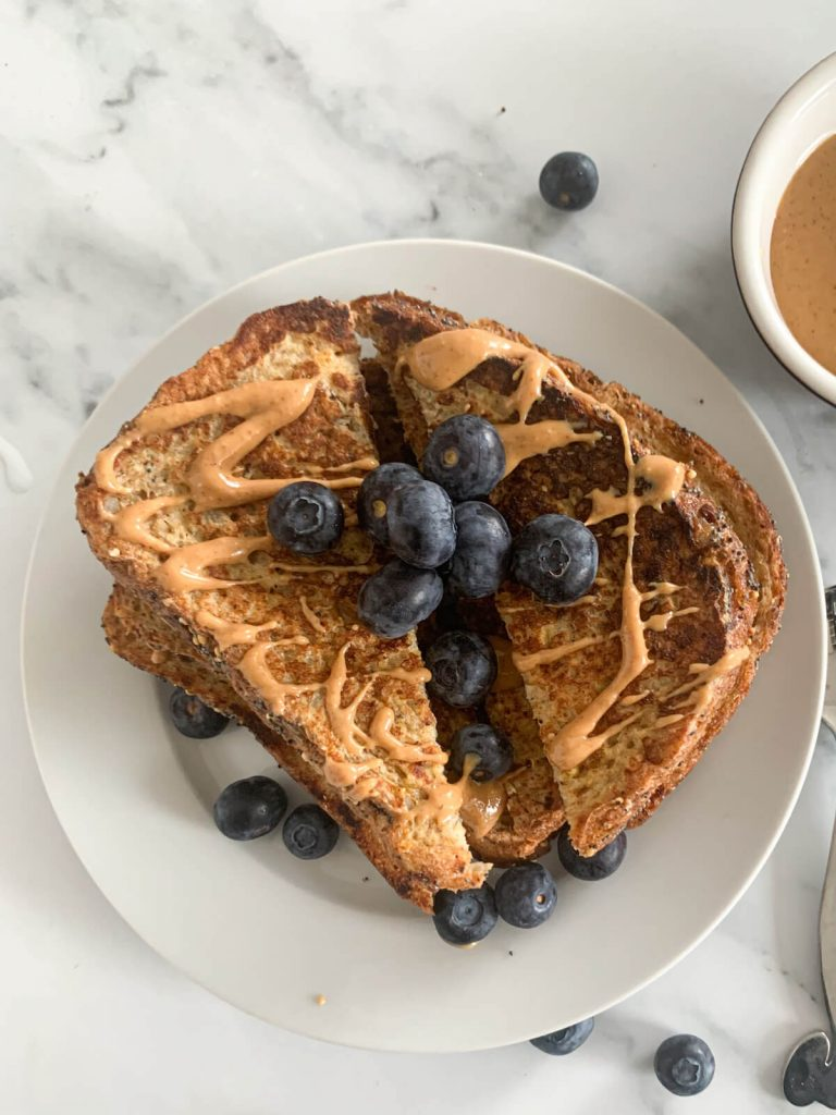 toast stacked one on top of other with blueberries and peanut butter
