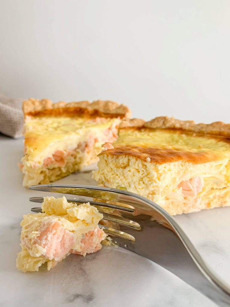 slice of salmon leek quiche with a fork cutting the end of it