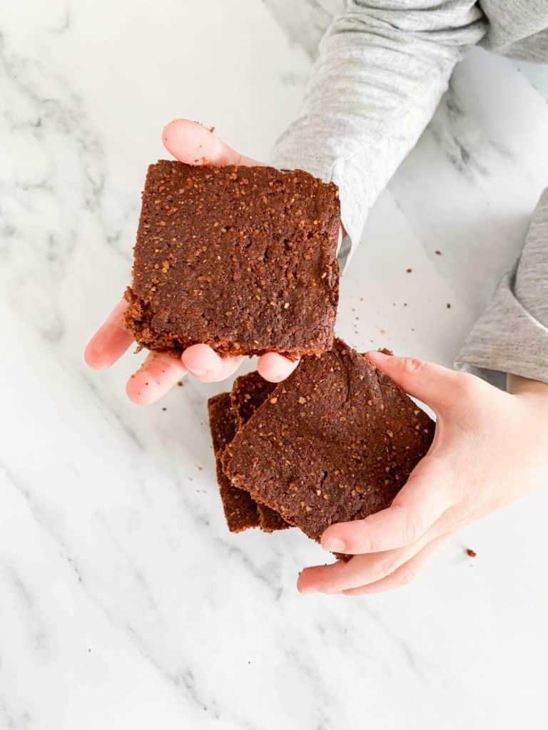 toddler holding 3 brownies