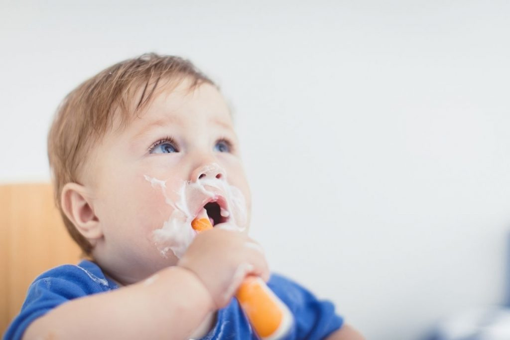 baby eating yoghurt with a spoon