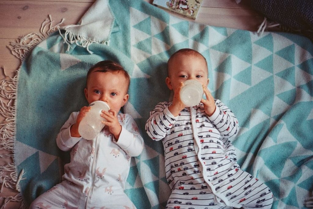 babies lying on a blanket drinking from a bottle