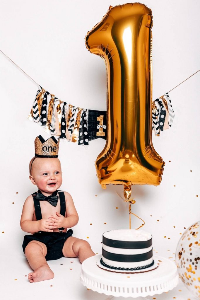 Baby sitting next to cake and a large balloon